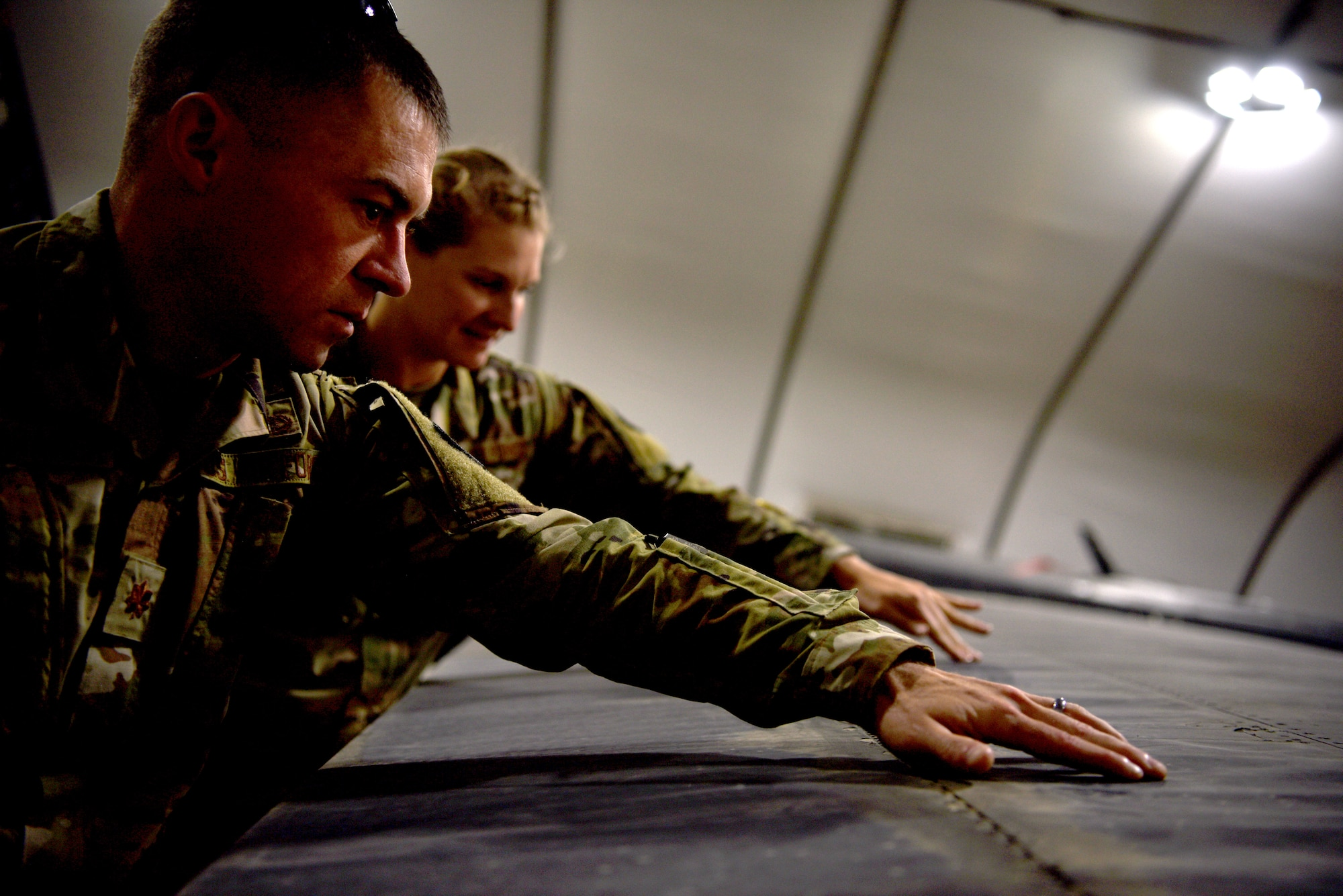 U.S. Air Force 1st Lt. M. Rebecca Kretzer, 380th Expeditionary Maintenance Group Depot Liaison Engineer, discusses potential maintenance requests during turnover with her replacement, Maj. Joseph Czabaranek, April 11, 2019.