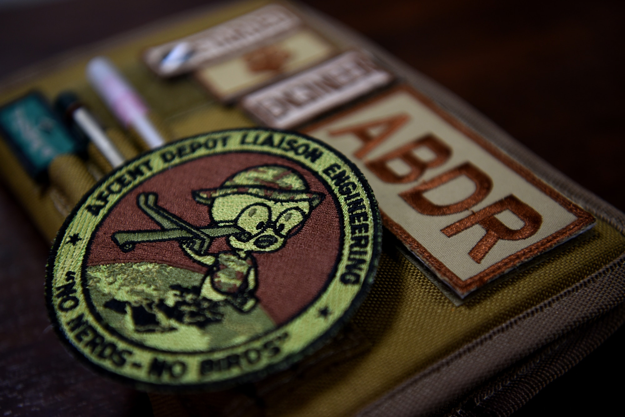 The unofficial unit Air Force Central Command Depot Liaison Engineering patch rests on a desk within the 380th Expeditionary Maintenance Group April 11, 2019.