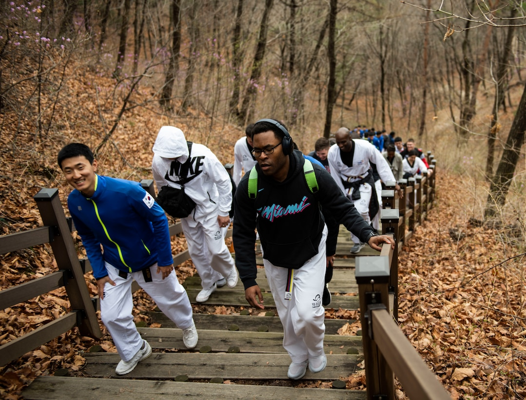 Members from the United States Forces-Korea and Republic of Korea Army hike up a hill during a Korean Ministry of Defense tour at Muju, Republic of Korea, April 9, 2019. One of the sites visited on the tour was an observatory that overlooks the city of Muju and is decorated with murals honoring the sport of Taekwondo. (U.S. Air Force photo by Senior Airman Stefan Alvarez)
