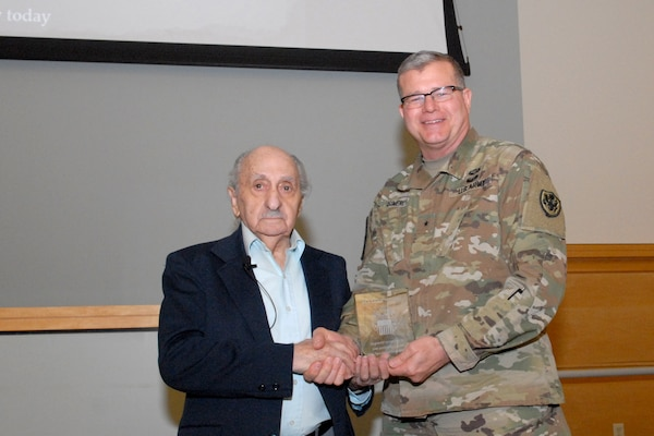 David Tuck, left, Holocaust survivor receives a plaque from Army Brig. Gen. Mark Simerly, DLA Troop Support commander, right, during the Holocaust Observance Program April 10 in Philadelphia. Tuck served as the keynote speaker for the event. (Photo by Ed Maldonado)