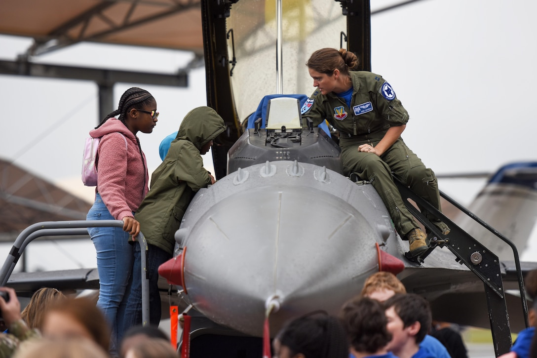 Children stand on some steps and look into the front of a military aircraft as a service member watches.