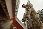 Staff Sgt. Sterling Benford, 557th Expeditionary RED HORSE Squadron supply NCO in charge, sweeps the edges of a large container in preparation for transport at Al Udeid Air Base, Qatar, April 3, 2019. Benford is responsible for the accountability of 1st Expeditionary Civil Engineer Group assets at deployed locations across U.S. Central Command (CENTCOM). Logistics Airmen were vital in the completion of more than 400 construction missions across the CENTCOM Theater during a six-month period. (U.S. Air Force photo by Tech. Sgt. Christopher Hubenthal)