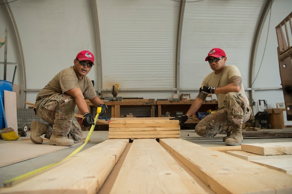 Tech. Sgt. Alexander Nunez, left, 557th Expeditionary RED HORSE Squadron air transportation NCO in charge, and Tech. Sgt. William Nicholas, right, 557th ERHS air transportation augmentee, construct an approach shoring at Al Udeid Air Base, Qatar, April 4, 2019. Nunez and Nicholas are responsible for facilitating air transportation for engineering assets needed across U.S. Central Command (CENTCOM). Logistics Airmen were vital in the completion of more than 400 construction missions across the CENTCOM Theater during a six-month period. (U.S. Air Force photo by Tech. Sgt. Christopher Hubenthal)