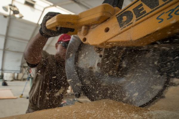Tech. Sgt. Alexander Nunez, 557th Expeditionary RED HORSE Squadron air transportation NCO in charge, cuts wood during the construction of an approach shoring at Al Udeid Air Base, Qatar, April 4, 2019. Nunez is responsible for facilitating air transportation for engineering assets needed across U.S. Central Command (CENTCOM). Logistics Airmen were vital in the completion of more than 400 construction missions across the CENTCOM Theater during a six-month period. (U.S. Air Force photo by Tech. Sgt. Christopher Hubenthal)