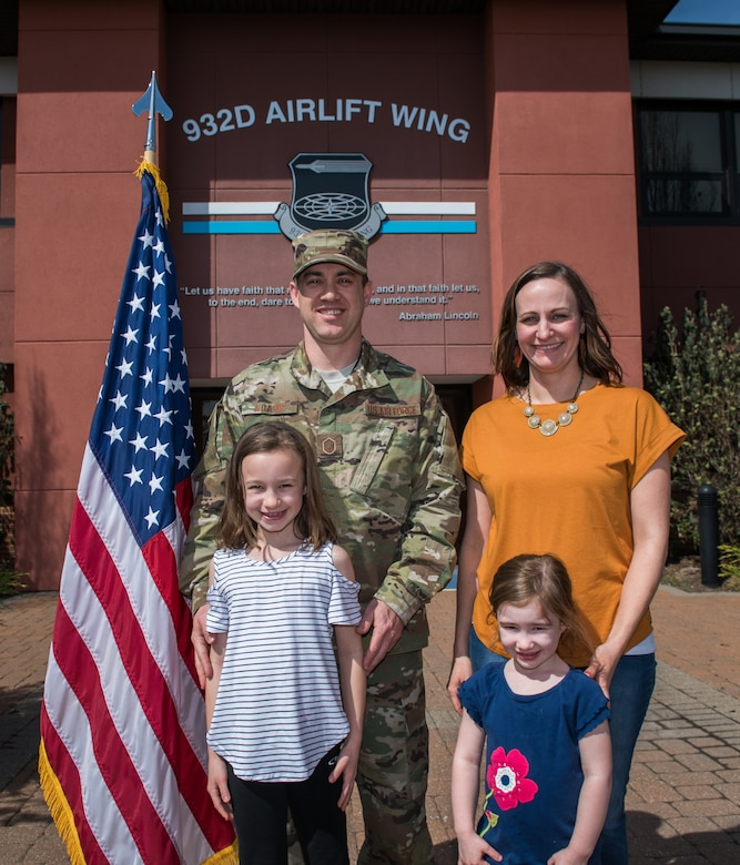 Master Sgt. Eric Adams, 932nd Airlift Wing flight safety noncommissioned officer in charge, is joined by his family following an outdoor enlistment ceremony April 7, 2019, Scott Air Force Base, Illinois. (U.S. Air Force photo by Master Sgt. Christopher Parr)