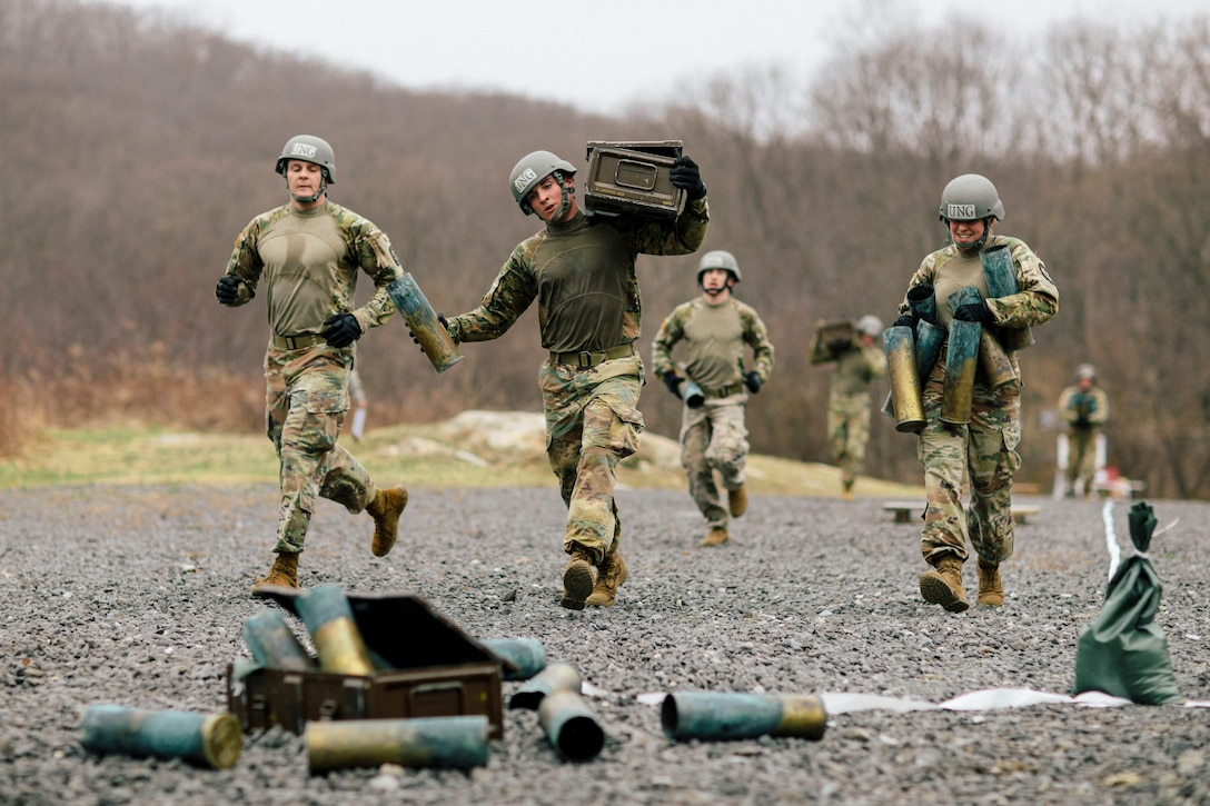 Cadets, including some carrying crates, run on gravel toward spent ammo cartridges.