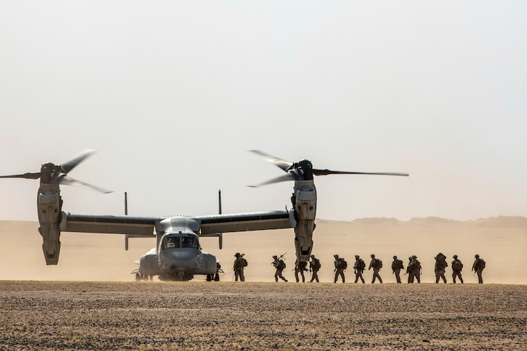 Marines and sailors walk in a line on desert terrain to a parked Osprey.