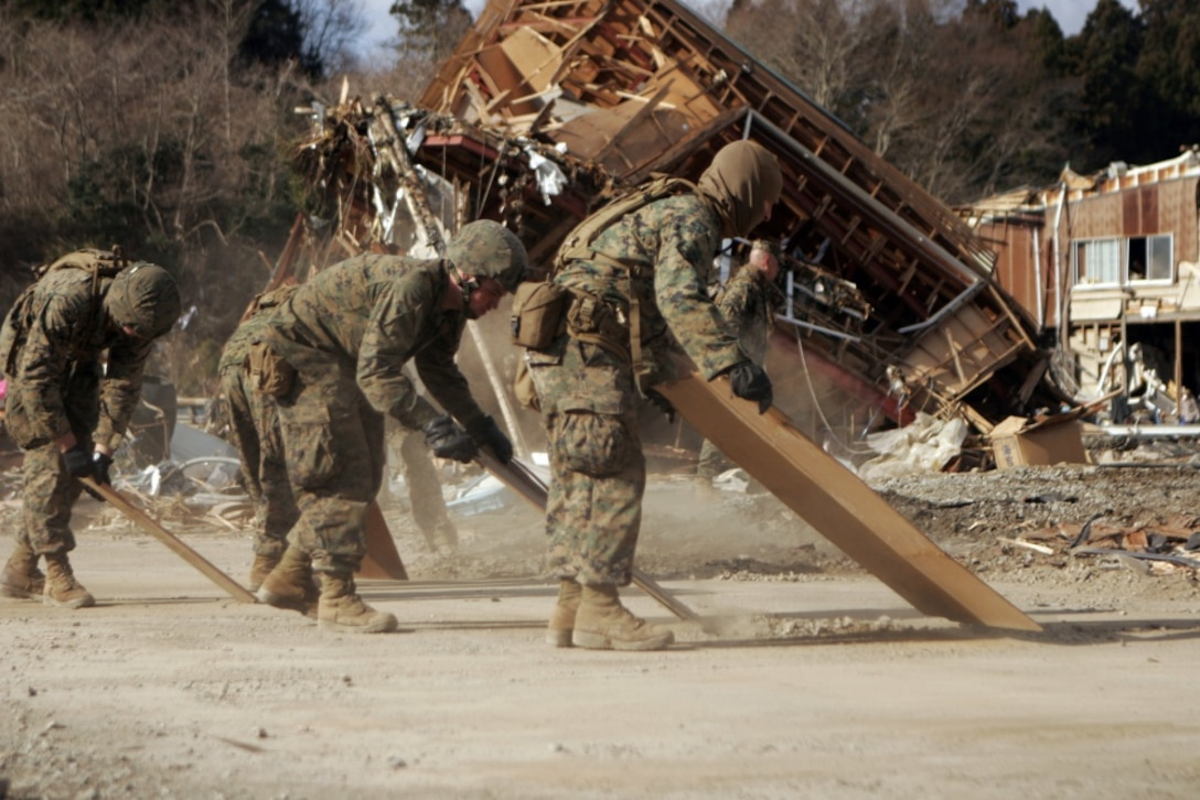 Marines clear debris off a road.
