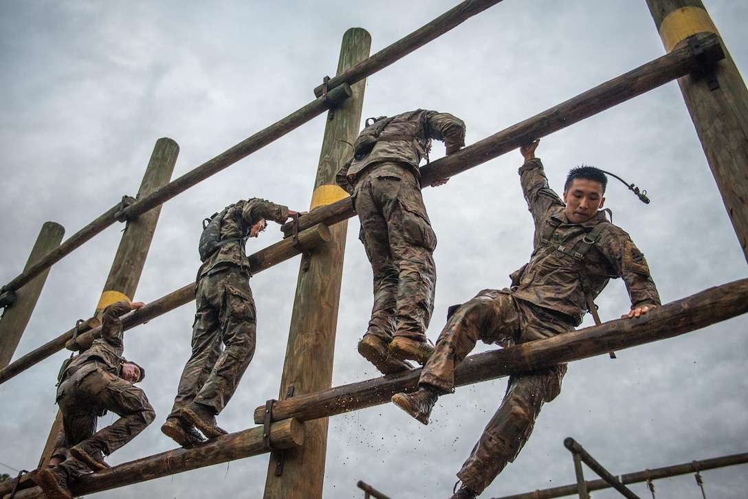Four soldiers climb on a wide wooden ladder.