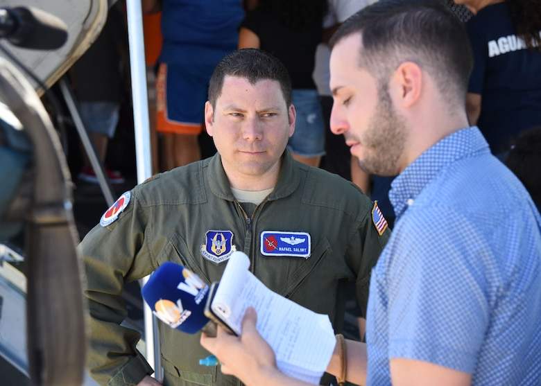 """Maj. Rafael Salort, 53rd Weather Reconnaissance Squadron navigator and mission commander, conducts an interview with media at the Rafael Hernández Airport, Aguadilla, Puerto Rico, April 13, 2019. NOAA hurricane specialists and the U.S. Air Force Reserve Hurricane Hunters discussed hurricane preparedness, resilience and how they can become """"weather-ready"""" during the 2019 Caribbean Hurricane Awareness Tour April 8-13, 2019. As part of the event dignitaries, students and the public toured the Air Force Reserve Command's WC-130J """"Hurricane Hunter"""" aircraft to learn how scientists collect hurricane information. (U.S. Air Force photo/Lt. Col. Marnee A.C. Losurdo)"""