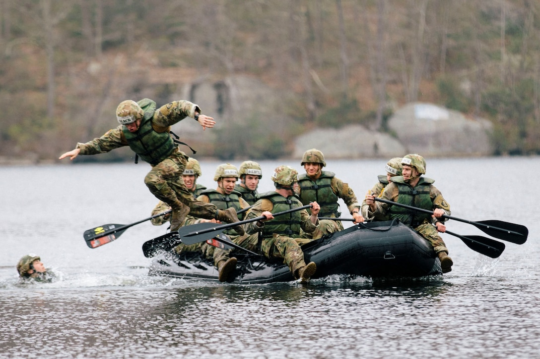 A group of soldiers paddle through water in a rubber boat as one soldier jumps into the water.
