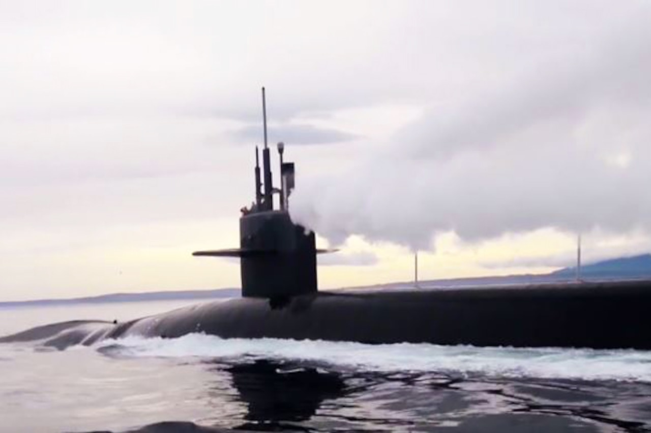 An image of the upper portion of a nuclear submarine in a body of water.