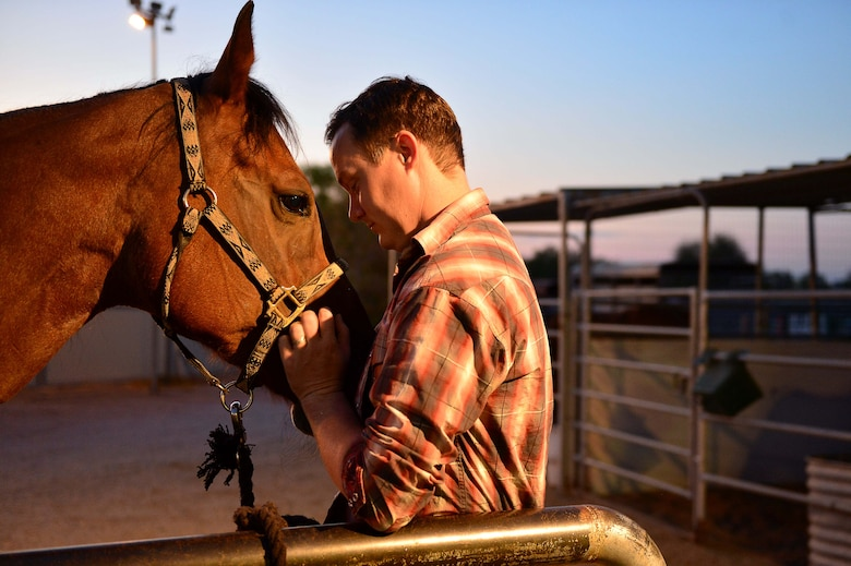 Maj. Travis, deputy of the 432nd Wing Staff Agency Commander's Action Group and survivor of an almost deadly motorcycle accident, greets his horse, Indy, in Las Vegas, Nevada, Aug. 14, 2018. Along with physical therapy after the crash, he credits a large part of that recovery to his horse, Indy. His motivation to gain back the rhythm, comfort level and physical conditioning he'd once had with her is what helped in building back his physical strength. (U.S. Air Force photo by Airman 1st Class Haley Stevens)