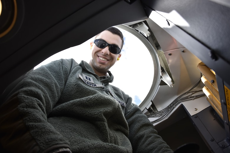 Capt.. Victor Traven, a systems and logistics class instructor from Wright Patterson Air Force Base, looks down from a latch opening inside a C-5 Galaxy parked on the tarmac at Westover Air Reserve Base.