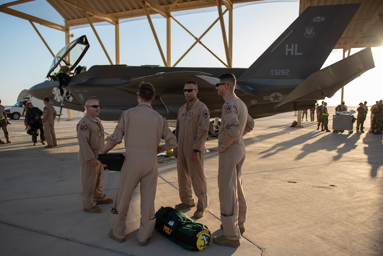 A photo of service members having a conversation next to an F-35A Lightning II