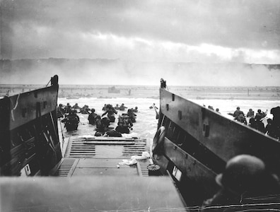 A Coast Guard-manned LCVP from the U.S.S. Samuel Chase disembarks troops of the First Division on the morning of 6 June 1944 at Omaha Beach