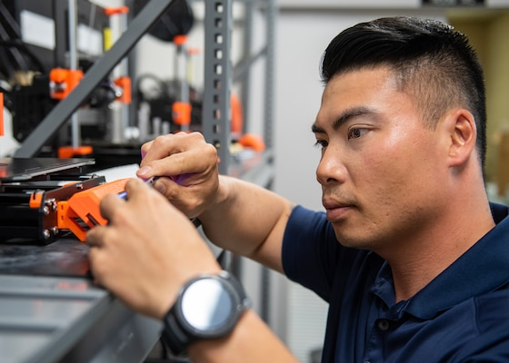 Naval Surface Warfare Center Panama City Division employee Bryan Tien Le uses a three dimensional printer to fabricate a part for one of the diver assisting units he works on. U.S. Navy photo by Eddie Green