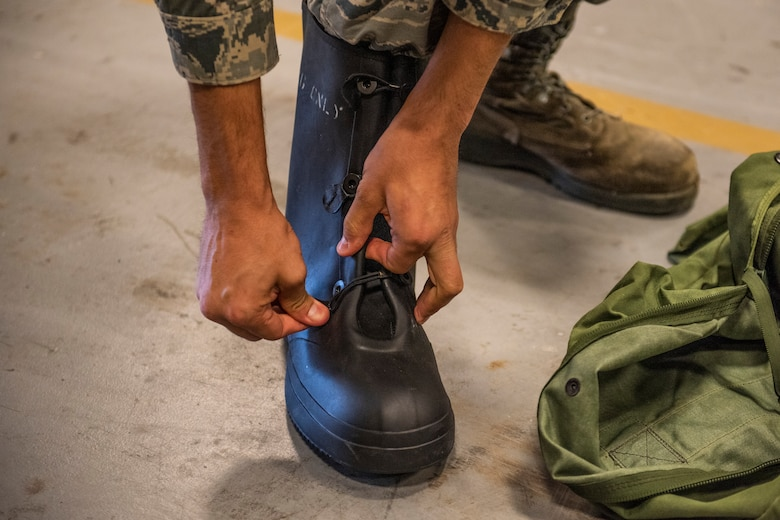 An Airman tries on a pair of boots April, 2, 2019 at Moody Air Force Base, Ga. From April 15-19, 2019, Moody executed a base-wide exercise that required players to function at a high operations tempo in a chemical, biological, radioactive and nuclear environment to meet Chief of Staff of the Air Force and the Commander of Air Combat Command's intent for readiness. (U.S. Air Force photo by Airman 1st Class Joseph P. Leveille)