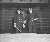 Coast Guard Captains Edward Fritzche (left) and Miles Imlay (right) discuss the invasion of Omaha Beach on a relief map laid out in the hold of the Samuel Chase.