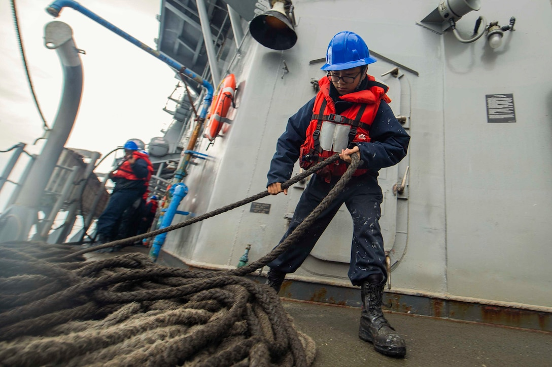 A sailor pulls a rope with a sailor working behind.