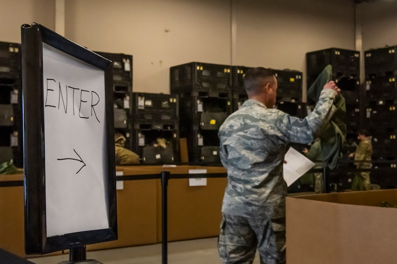 An Airman picks up a bag for his MOPP gear April 2, 2019, at Moody Air Force Base, Ga. From April 15-19, 2019, Moody executed a base-wide exercise that required players to function at a high operations tempo in a chemical, biological, radioactive and nuclear environment to meet Chief of Staff of the Air Force and the Commander of Air Combat Command's intent for readiness. (U.S. Air Force photo by Airman 1st Class Joseph P. Leveille)