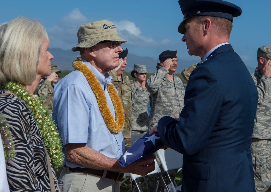 Col. Halsey Burks, 15th Wing commander, gives an American Flag to Bob Harris, during a memorial service held for retired Master Sgt. Byram Bates at the Missing Man Memorial on Joint Base Pearl Harbor-Hickam, Hawaii, April 12, 2019. Harris is the closest living member to Bates, who was a survivor of the Dec. 7, 1941 attack. (U.S. Air Force photo by Tech. Sgt. Heather Redman)