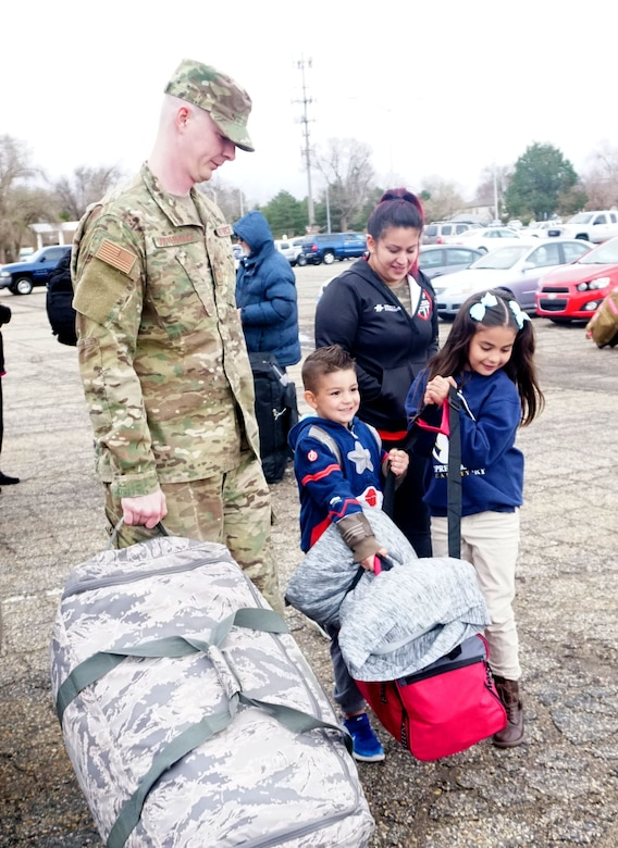 Hunter and Juliana, children of Tech. Sgt. Dylan Oosterhouse and wife Anna, help load their dad's deployment bags at Hill Air Force Base, Utah