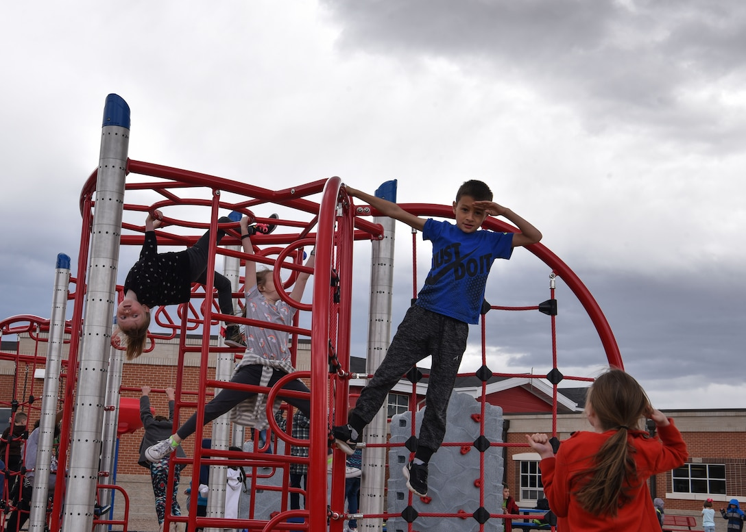 Reagan salutes a classmate from the top of a jungle gym, April 15, 2019, in Cheyenne, Wyo. While his understanding of the military is limited he knows what his mom is doing is important and he is proud that she is in the military. (U.S. Air Force photo by Airman 1st Class Braydon Williams)