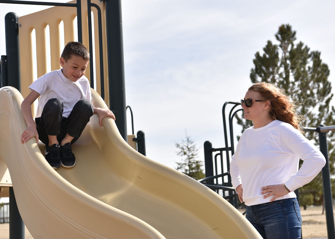 Airman 1st Class Megan Melvin, 90th Communications Squadron knowledge operations, watches her son, Reagan, while he plays on a playground, April 6, 2019, on F.E. Warren Air Force Base, Wyo. Reagan and his mom are the best of friends, even though they don't get to spend as much time together as they would like. (U.S. Air Force photo by Airman 1st Class Braydon Williams)