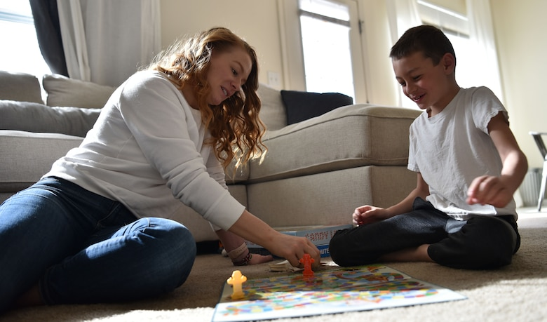 Airman 1st Class Megan Melvin, 90th Communications Squadron knowledge operations, and her son Reagan, play a board game after school, April 6, 2019, on F.E. Warren Air Force Base, Wyo. Megan works hard to balance work and home life but has found that one side of life will always be stronger than the other. (U.S. Air Force photo by Airman 1st Class Braydon Williams)