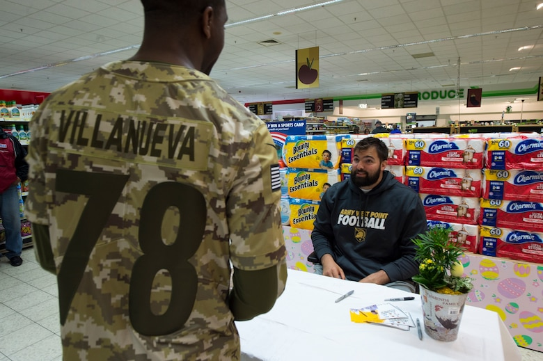 Alejandro Villanueva, Pittsburgh Steelers offensive lineman, talks to a Kaiserslautern Military Community member during an autograph session at the commissary on Vogelweh Military Complex, April 13, 2019. Villanueva, a former U.S. Army captain and Army Ranger, was awarded the Bronze Star medal with valor for his actions during a deployment to Afghanistan. (U.S. Air Force photo by Staff Sgt. Jonathan Bass)