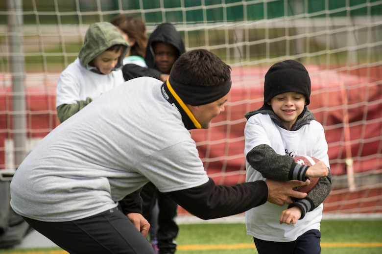 A volunteer coach hands the ball off to an Alejandro Villanueva football camp attendee during offensive drills at Kaiserslautern High School on Vogelweh Military Complex, Germany, April 13, 2019. Volunteer coaches from around the Kaiserslautern Military Community coached young football players on offensive and defensive drills, along with seven-on-seven games. (U.S. Air Force photo by Staff Sgt. Jonathan Bass)