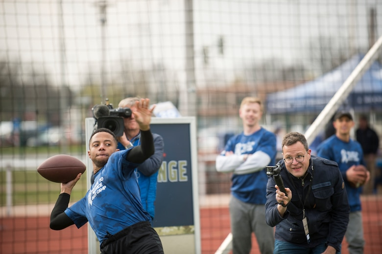 An Alejandro Villanueva football camp attendee throws a football while NBC Europe videographers film during a football distance throw drill at Kaiserslautern High School on Vogelweh Military Complex, Germany, April 13, 2019. Villanueva, Pittsburgh Steelers offensive lineman, served in the U.S. Army before becoming a professional football player. (U.S. Air Force photo by Staff Sgt. Jonathan Bass)