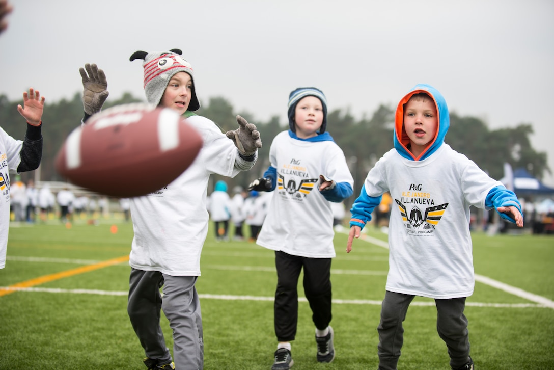 Alejandro Villanueva football camp attendees attempt to catch a football while practicing offensive drills during the Alejandro Villanueva football camp at Kaiserslautern High School on Vogelweh Military Complex, Germany, April 14, 2019. More than 200 children participated in the two-day camp focusing on football fundamentals. (U.S. Air Force photo by Staff Sgt. Jonathan Bass)