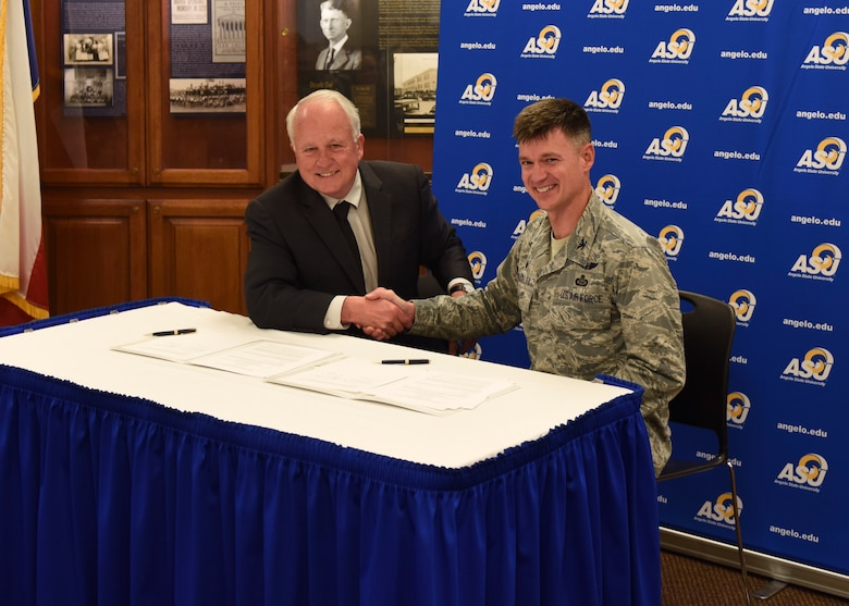 Angelo State University President, Dr. Brian May and U.S. Air Force Col. Thomas Coakley, 17th Training Group commander, shake hands after signing the Memorandum of Understanding at ASU, Texas, April 15, 2019. The MOU allows 14N professionals to transfer 12 credit hours toward two master's degree through Angelo State University (U.S. Air Force photo by Airman 1st Class Zachary Chapman/Released)
