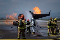 A team comprised of Central American firefighters extinguish a flame in a simulated helicopter during the Central America Sharing Mutual Operational Knowledge and Experiences (CENTAM SMOKE) exercise, April 1, 2019, at Soto Cano Air Base, Honduras. CENTAM SMOKE brought together firefighters from Honduras, Costa Rica, Belize, Guatemala and El Salvador to train with U.S. Air Force members as well as develop bonds and understandings of one another's culture with team building exercises. The weeklong training included aircraft and structural fires, vehicle extrication, and a firefighter combat challenge. (U.S. Air Force photo by Staff Sgt. Eric Summers Jr.)