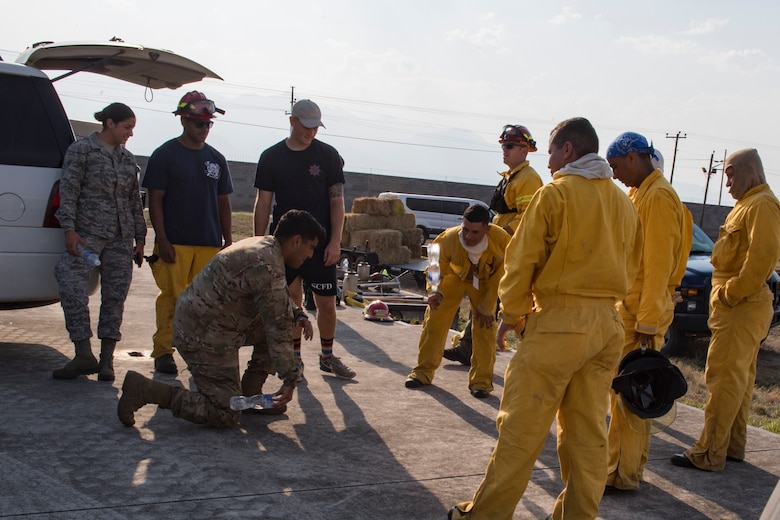 A group of U.S. Air Force and Central American firefighters relax after extinguishing a wildlands fire during the Central America Sharing Mutual Operational Knowledge and Experiences (CENTAM SMOKE) exercise, April 11, 2019, at Soto Cano Air Base, Honduras. CENTAM SMOKE brought together firefighters from Honduras, Costa Rica, Belize, Guatemala and El Salvador to train with U.S. Air Force members as well as develop bonds and understandings of one another's culture with team building exercises. The weeklong training included aircraft and structural fires, vehicle extrication, and a firefighter combat challenge. (U.S. Air Force photo by Staff Sgt. Eric Summers Jr.)