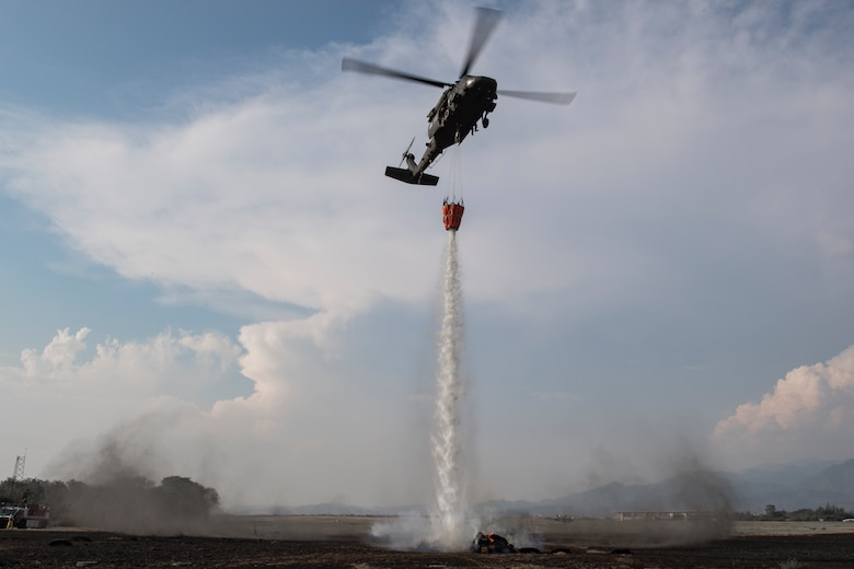 A UH-60 Blackhawk from the 1-228th Aviation Regiment aims to extinguish a simulated wildfire to show the additional capabilities of Joint Task Force - Bravo during the Central America Sharing Mutual Operational Knowledge and Experiences (CENTAM SMOKE) exercise, April 11, 2019, at Soto Cano Air Base, Honduras. CENTAM SMOKE brought together firefighters from Honduras, Costa Rica, Belize, Guatemala and El Salvador to train with U.S. Air Force members as well as develop bonds and understandings of one another's culture with team building exercises. The weeklong training included aircraft and structural fires, vehicle extrication, and a firefighter combat challenge. (U.S. Air Force photo by Staff Sgt. Eric Summers Jr.)