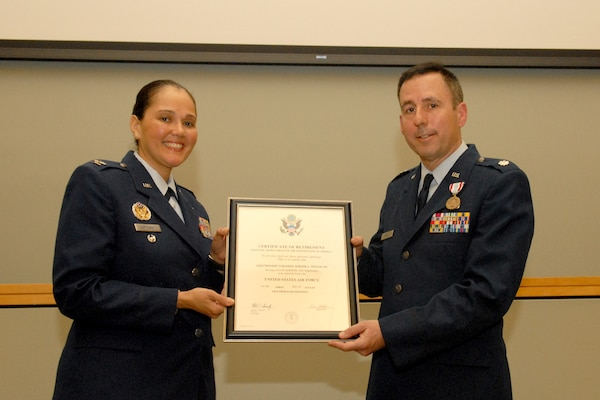 Air Force Col. Mary Ann Garbowski, Air Force Medical Operations Agency Medical Logistics director, left, and Lt. Col. Roger Willis, DLA Troop Support Medical supply chain's Institutional Customer Facing Division chief, right, pose with Willis' retirement certificate during a ceremony at DLA Troop Support April 12, 2019 in Philadelphia.
