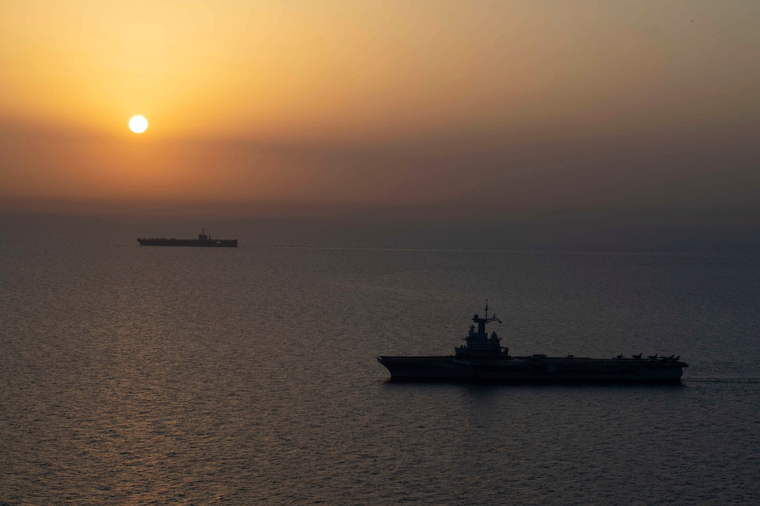 Two ships travel in the sea, against an orange sky.