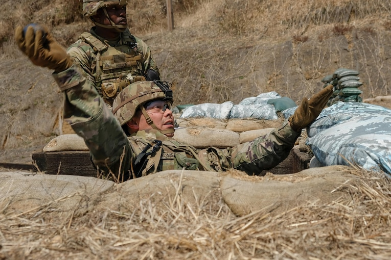 A soldier in a hole throws a training hand grenade.