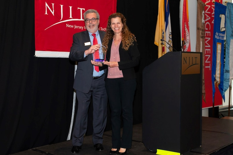 Michele Huk, team lead for the NAWCAD Lakehurst Workforce Development Team, accepts the New Jersey Institute of Technology's Top Full Time Employer of the Year Award from Greg Mass, executive director of Career Development Services at NJIT.