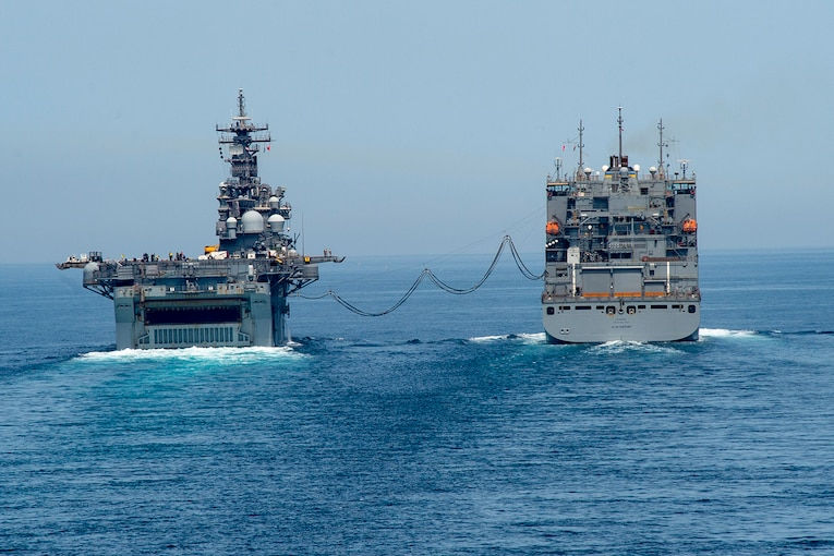 Two ships conduct a replenishment at sea.