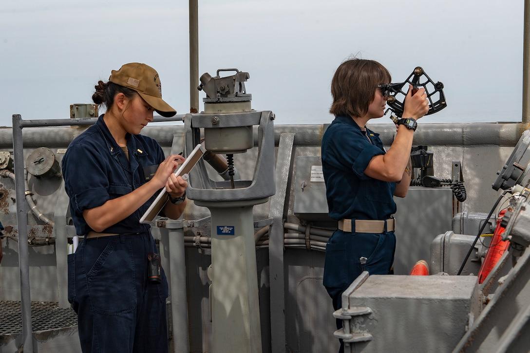 Sailors record distances during a replenishment at sea.