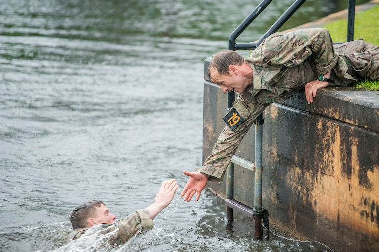 A soldier reaches to help another soldier out of the water.