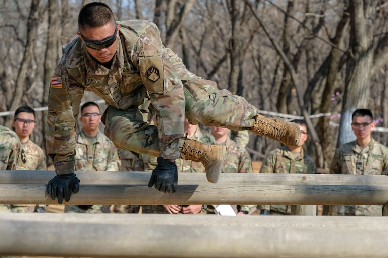 A soldier jumps over a wooden obstacle during a competition.