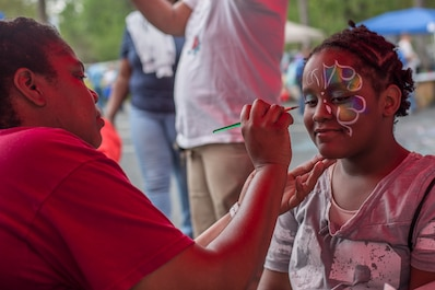 Tamika Curtis paints a child's face during KidFest in Beaufort, April 6. Curtis is a program assistant with Marine Corps Community Services South Carolina.