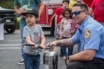 A Beaufort Fire Department member helps a child with a fire extinguisher drill at KidFest in Beaufort, April 6. KidFest is held to raise awareness for Child Abuse Prevention Month while also celebrating the Month of the Military Child with the local community.