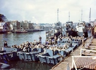Coast Guard Flotilla 10 tied up in the background along with British landing craft, prepare to sail the English Channel and invade Nazi-occupied France. These landing craft landed U.S. troops on Omaha Beach.