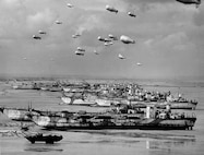 British LCT's line the Normandy shore, each with a barrage balloon designed to discourage enemy air attack.